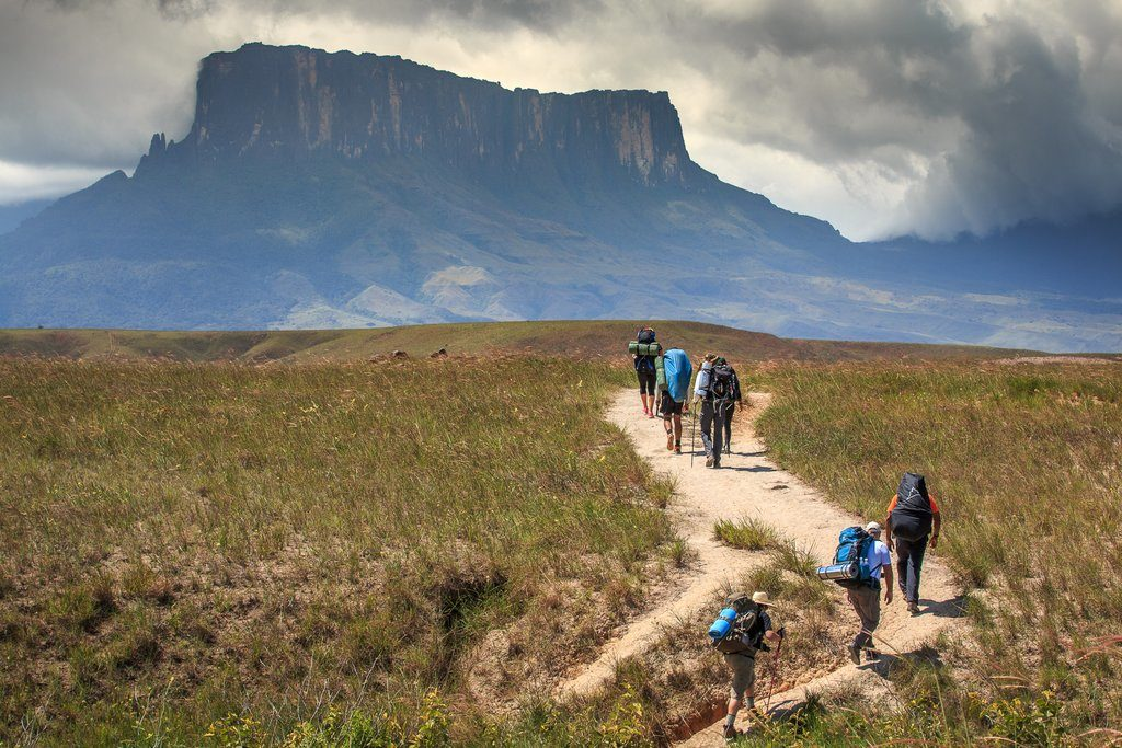 Hikers follow a trail far below the touring plateau of Mt. Roraima.