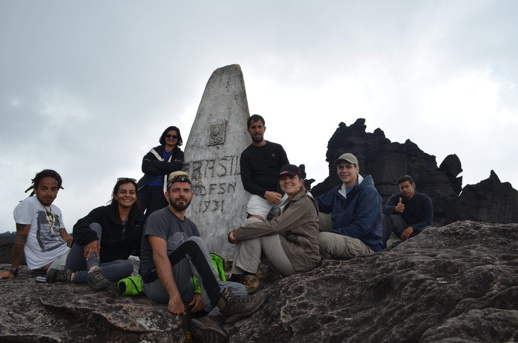 Hikers sit at the base of the tripoint among craggy rock features.